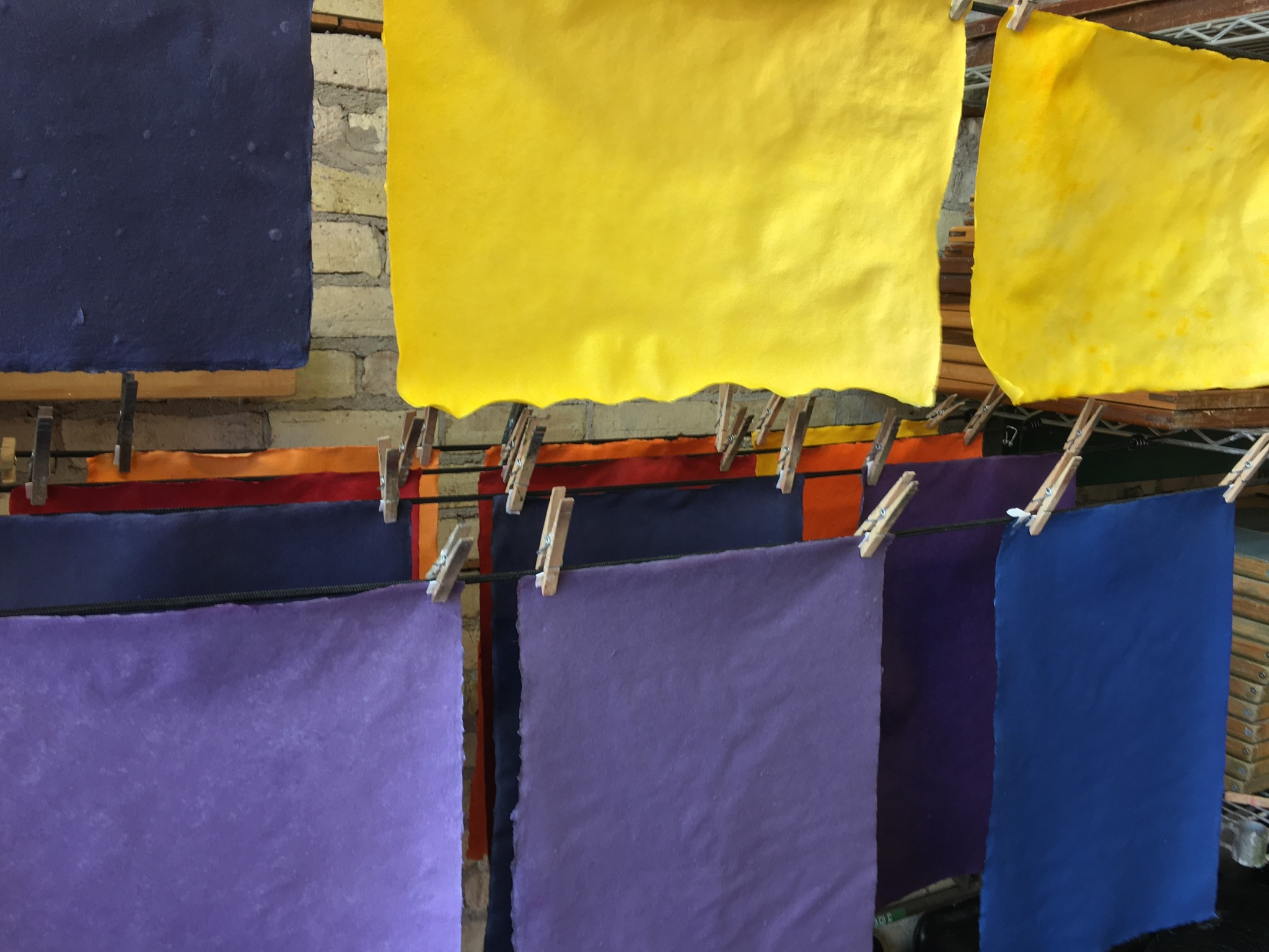 Handmade sheets of paper drying after the colouring process.